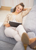 Happy young woman laying on divan and using tablet pc Royalty Free Stock Photography
