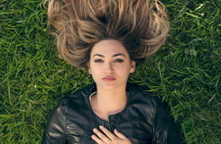 Happy young woman laying on the grass in park Royalty Free Stock Images
