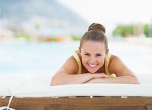 Happy young woman laying on sunbed Royalty Free Stock Image