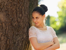Happy young woman lean against tree in park Royalty Free Stock Photography