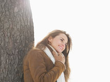 Happy young woman leaning against tree in winter park Royalty Free Stock Photography