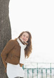 Happy young woman leaning against tree in winter park Royalty Free Stock Images
