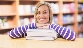 Happy young woman leaning on book at desk. Portrait of happy young woman leaning on book at desk in library Royalty Free Stock Images
