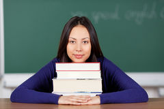 Happy young woman leaning head on books Royalty Free Stock Images