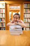 Happy young woman leaning on stack of book. Portrait of happy young woman leaning on stack of book in library at college Stock Photography