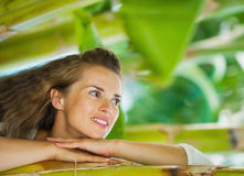 Happy young woman leaning on tropical palm Stock Photography