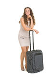 Happy young woman leaning on wheels suitcase Stock Photo
