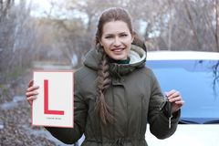 Happy young woman with learner driver sign. And car key outdoors Royalty Free Stock Image