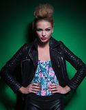 Happy young woman in leather jacket with hands on hips smiles Stock Photography