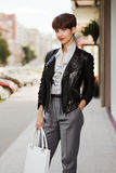 Happy young fashion woman in leather jacket with handbag Stock Images