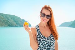 Happy young woman with lemon by the sea on a sunny day Stock Image