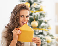 Happy young woman licking envelope in front of christmas tree Royalty Free Stock Images