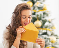 Happy young woman licking envelope near christmas tree Royalty Free Stock Images