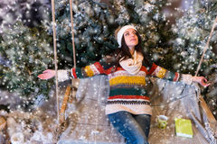 Happy young woman lie down with arms outstretched on a swing in. Happy young woman lie down with arms outstretched on a swing with book and cup on it in a snow Stock Photo