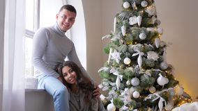 Happy young woman lies on feet of her husband near window in room beside decorated xmas tree, New Year`s Eve. Happy young woman with artificial snow on hair lies stock footage