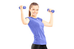 Happy young woman lifting dumbbells Royalty Free Stock Photos