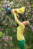 Happy young woman lifting her son high up Stock Images