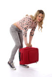 Happy Young Woman Lifting a Red Suitcase Royalty Free Stock Images