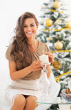 Happy young woman lighting candle near christmas tree Royalty Free Stock Photography