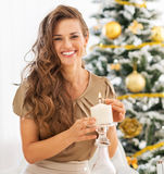 Happy young woman lighting candle near christmas tree Stock Photo