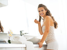 Happy young woman with lip gloss in bathroom Stock Image