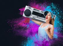 Happy young woman listening music with boombox. Against powder explosion background Stock Photos