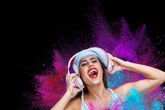 Happy young woman listening music in headphones Stock Images