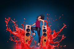 Happy young woman listening music with speakers. Happy young woman listening music with loud speakers in front of liquid splash explosion background royalty free stock image