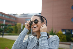 Happy young woman listening music outdoor. By headphones Stock Image