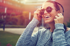 Happy young woman listening music outdoor. By headphones in sunset Royalty Free Stock Images