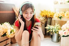 Happy Young Woman Listening Music From Smart Phone in Cozy House Stock Images