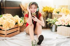 Happy Young Woman Listening Music From Smart Phone in Cozy House Royalty Free Stock Photo