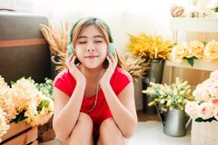 Happy Young Woman Listening Music From Smart Phone in Cozy House Royalty Free Stock Image