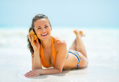 Happy young woman listening sound of sea Stock Photos