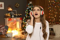 Happy young woman listening to Christmas music. At home royalty free stock image