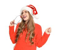 Happy young woman listening to Christmas music. On white background royalty free stock photography