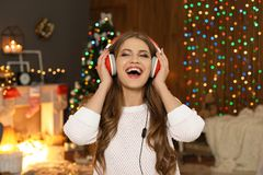 Happy young woman listening to Christmas music. At home royalty free stock photography