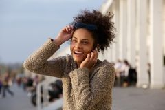 Happy young woman listening to music on earphones Stock Image