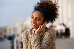 Happy young woman listening to music on earphones outdoors Royalty Free Stock Photo