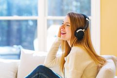 Happy young woman listening to music on headphones. At home Stock Image