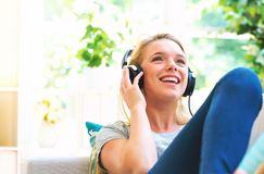 Happy young woman listening to music on headphones. At home Stock Photo