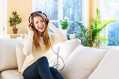 Happy young woman listening to music on headphones Stock Image