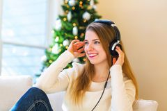 Happy young woman listening to music on headphones. At home Stock Photography