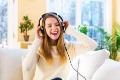 Happy young woman listening to music on headphones. At home Royalty Free Stock Image