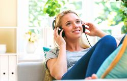 Happy young woman listening to music on headphones. At home Royalty Free Stock Photo