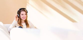 Happy young woman listening to music on headphones. At home Stock Photos