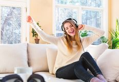 Happy young woman listening to music on headphones Royalty Free Stock Image