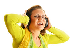 Happy young woman listening to the music in headphones isolated Stock Photography