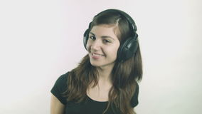 Happy young woman listening to music on headphones stock video
