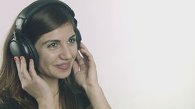 Happy young woman listening to music on headphones stock footage